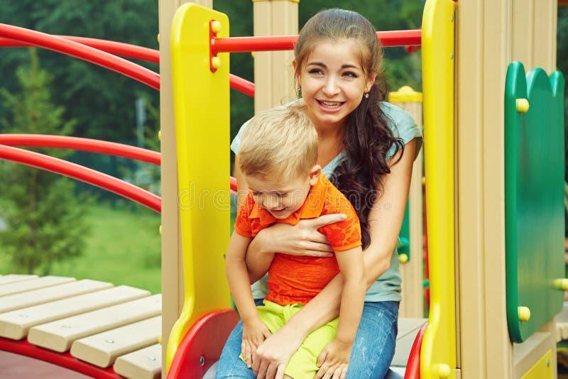 αγόρι λίγη παιδική χαρά παίζοντας παιδί με τη μητέρα σε μια φωτογραφική διαφάνεια στοκ εικόνα