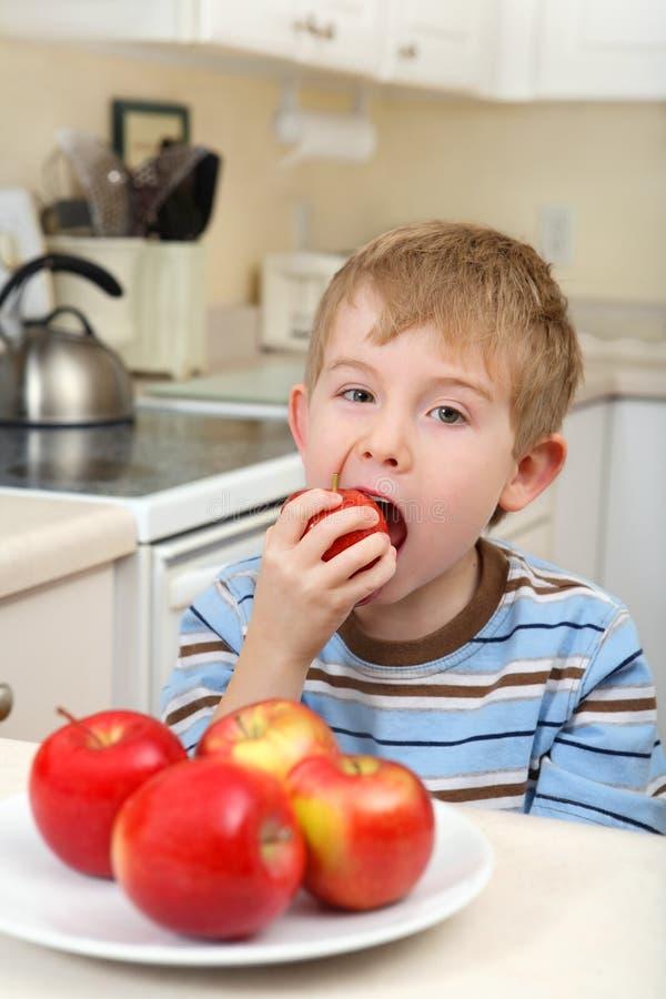 αγόρι μήλων που τρώει τις νεολαίες στοκ φωτογραφία με δικαίωμα ελεύθερης χρήσης