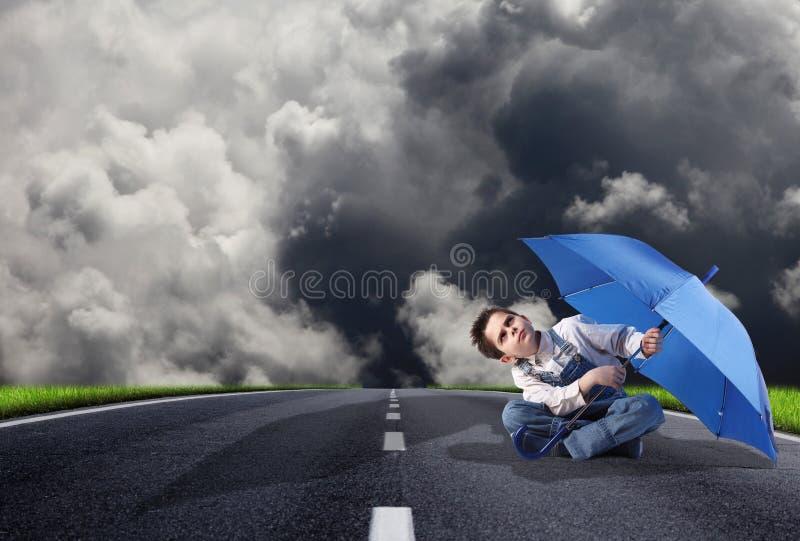 Αγόρι με μια ανοικτή ομπρέλα που ανατρέχει στοκ φωτογραφίες