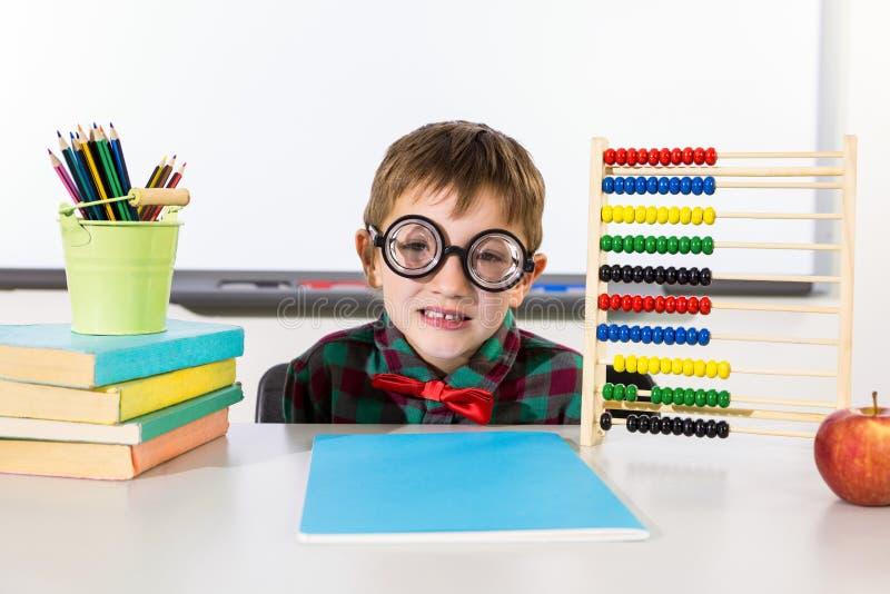 Αγόρι με τα βιβλία και άβακας στην τάξη στοκ εικόνες με δικαίωμα ελεύθερης χρήσης