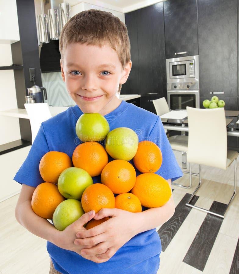 Αγόρι με τα μήλα και τα πορτοκάλια στοκ φωτογραφία