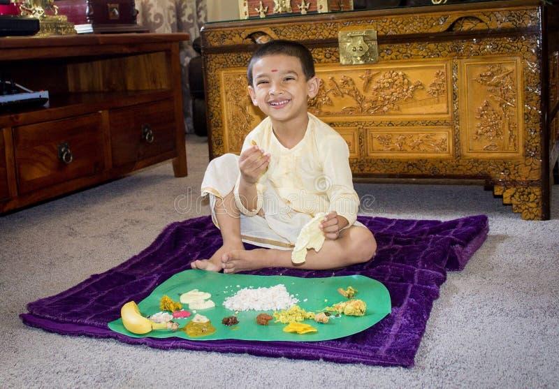Αγόρι με τα παραδοσιακά ενδύματα την ημέρα και την κατοχή onam του μεσημεριανού γεύματος στοκ φωτογραφίες
