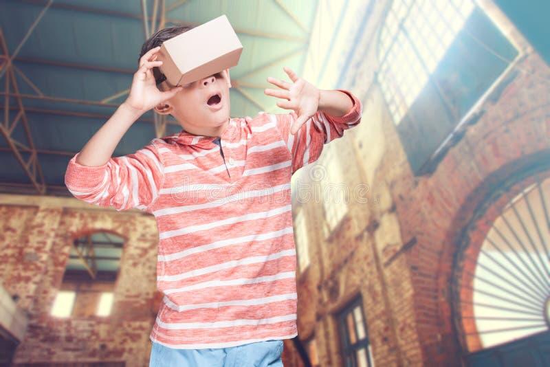 Αγόρι με την κάσκα χαρτονιού εικονικής πραγματικότητας DIY στοκ φωτογραφία