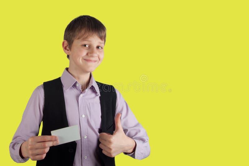Αγόρι με την πιστωτική κάρτα στο κίτρινο υπόβαθρο στοκ φωτογραφία με δικαίωμα ελεύθερης χρήσης