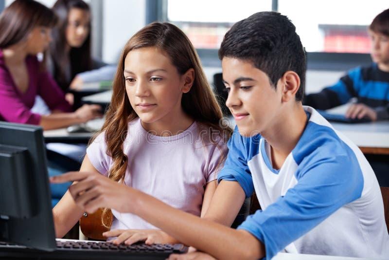 Αγόρι με τη θηλυκή υπόδειξη φίλων στη οθόνη υπολογιστή στοκ φωτογραφία με δικαίωμα ελεύθερης χρήσης