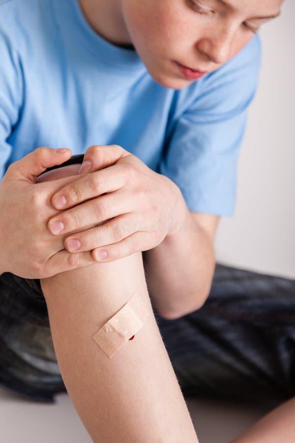 Αγόρι με τον επίδεσμο που καλύπτει την πληγή στο αντικνήμιο στοκ φωτογραφίες