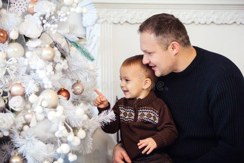 Αγόρι με τον πατέρα κοντά στο χριστουγεννιάτικο δέντρο στοκ εικόνα με δικαίωμα ελεύθερης χρήσης