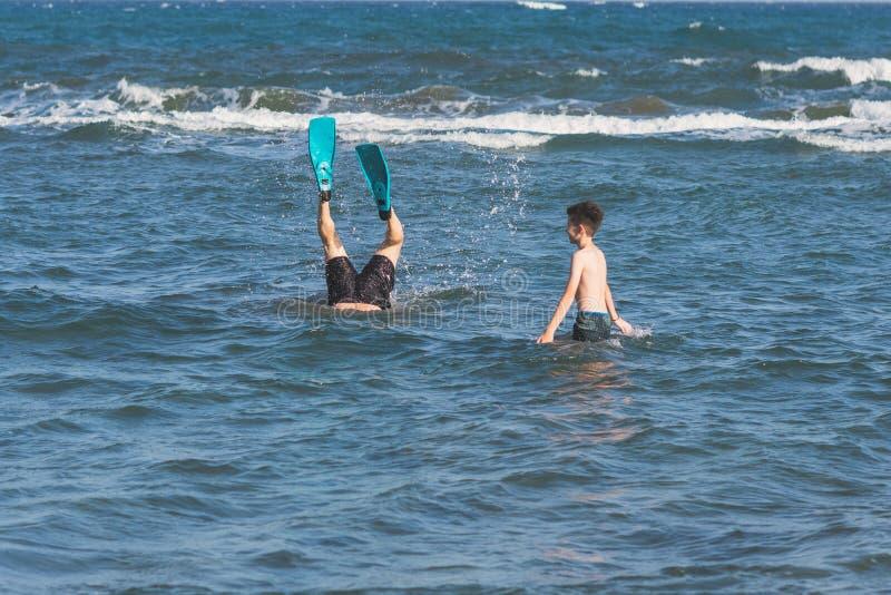 Αγόρι με το βουτώντας πατέρα στα κολυμπώντας βατραχοπέδιλα επάνω από τα κύματα θύελλας στοκ φωτογραφίες με δικαίωμα ελεύθερης χρήσης