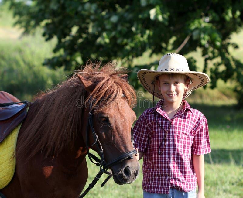 Αγόρι με το καπέλο κάουμποϋ και άλογο στοκ εικόνες