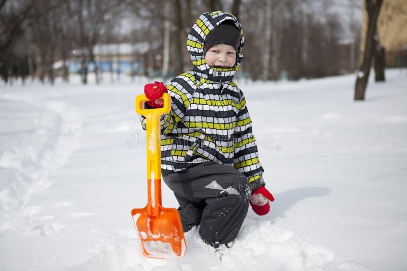 Αγόρι με το μεγάλο φτυάρι για να καθαρίσει το χιόνι στοκ εικόνες με δικαίωμα ελεύθερης χρήσης