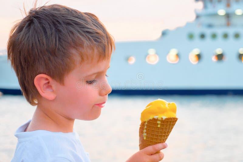 Αγόρι με το παγωτό με το γιοτ στο υπόβαθρο Γλυκό υπόβαθρο τροφίμων Παιδί που τρώει το παγωτό στην ακτή με το πορθμείο στοκ φωτογραφίες με δικαίωμα ελεύθερης χρήσης