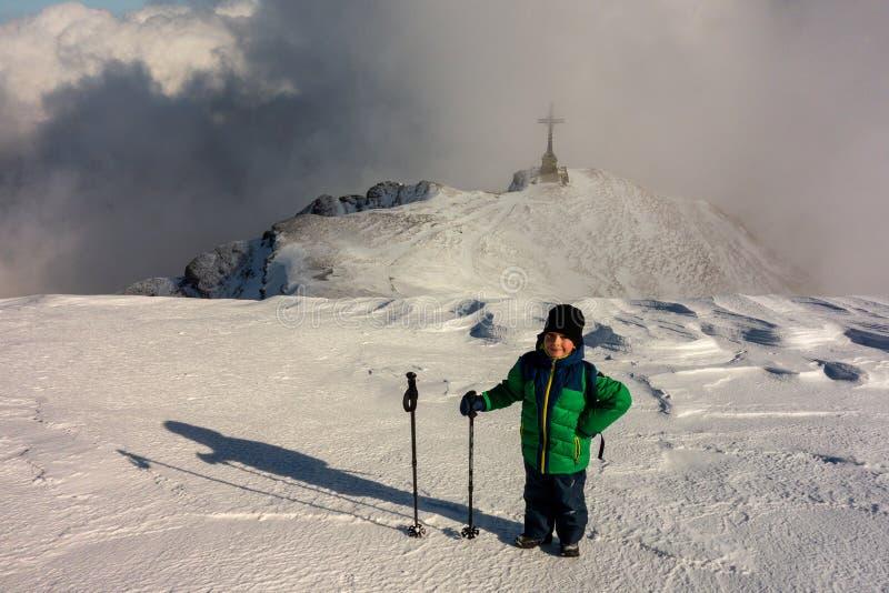 Αγόρι με το περπάτημα των πόλων που επισκέπτονται ένα μνημείο στο βουνό στοκ εικόνες