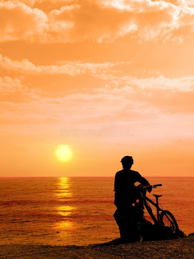 Αγόρι με το ποδήλατό του που στηρίζεται και που εξετάζει τη θάλασσα στοκ εικόνες