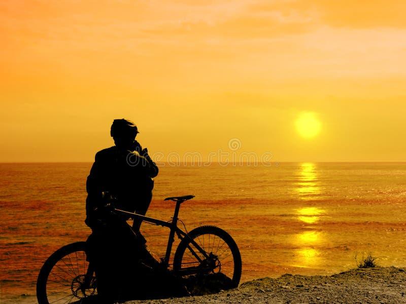 Αγόρι με το ποδήλατό του που στηρίζεται και που εξετάζει τη θάλασσα στοκ φωτογραφία