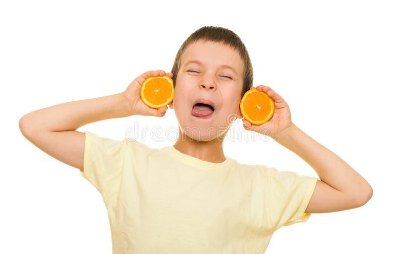 Αγόρι με το τεμαχισμένο πορτοκάλι που έχει τη διασκέδαση στοκ φωτογραφία με δικαίωμα ελεύθερης χρήσης
