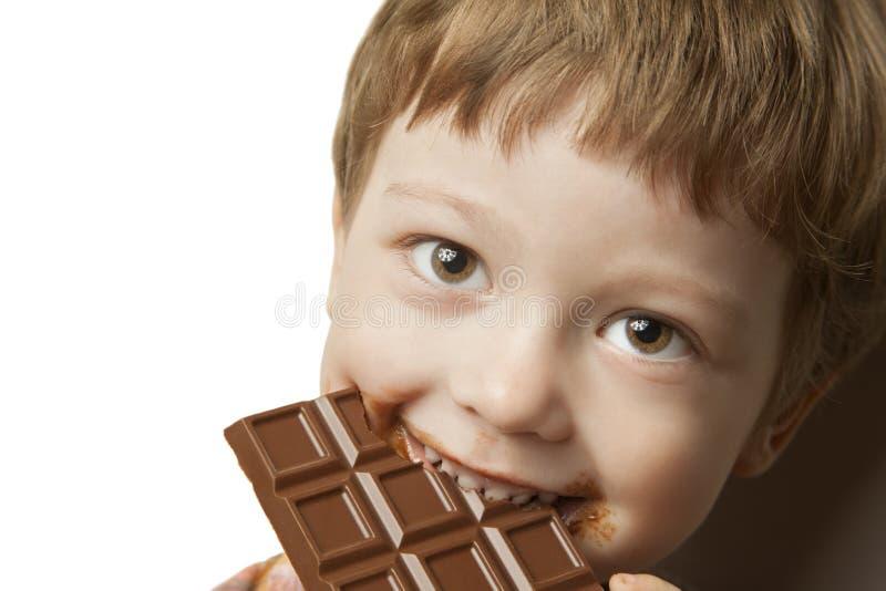 αγόρι με το φραγμό σοκολάτας στοκ εικόνες