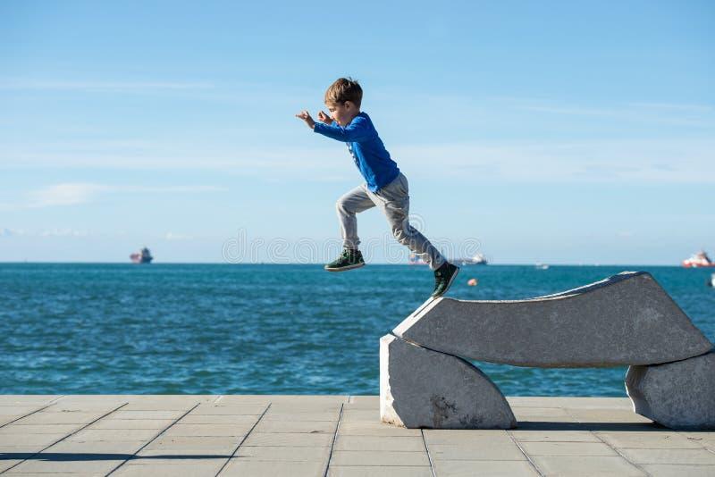 Αγόρι μικρών παιδιών που πηδά από ένα γλυπτό πετρών θαλασσίως στοκ εικόνα