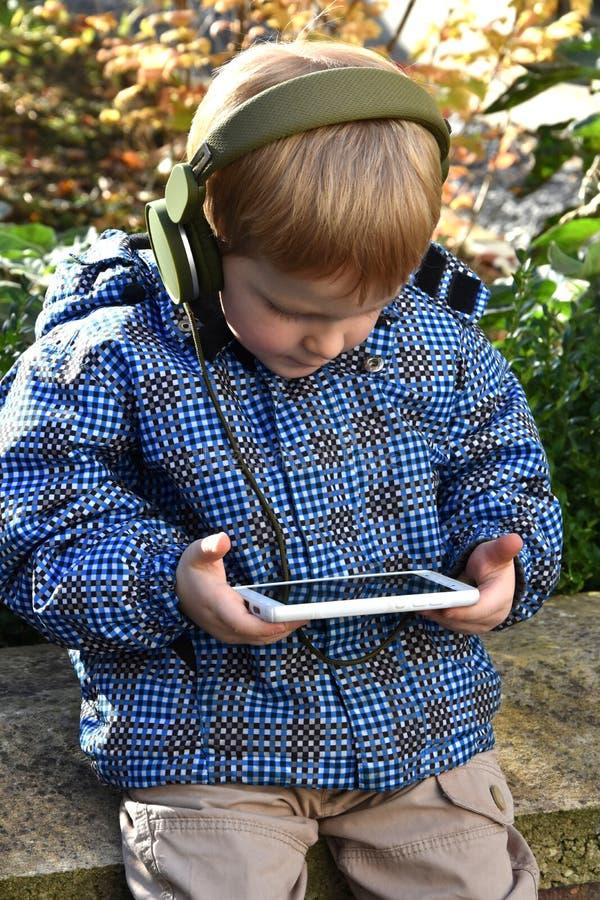 Αγόρι μικρών παιδιών με το έξυπνος-τηλέφωνο στοκ εικόνα
