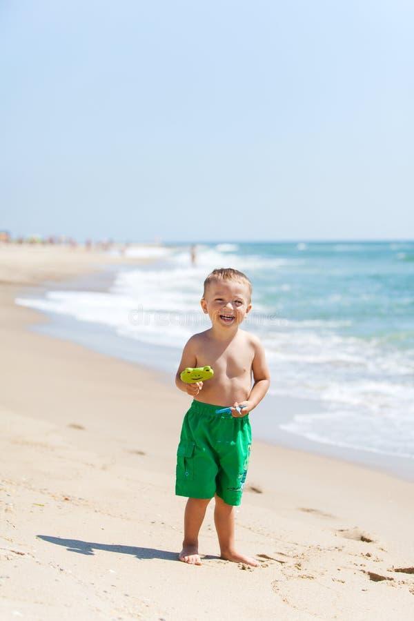 Αγόρι μικρών παιδιών στην παραλία με την καραμέλα στοκ εικόνα με δικαίωμα ελεύθερης χρήσης