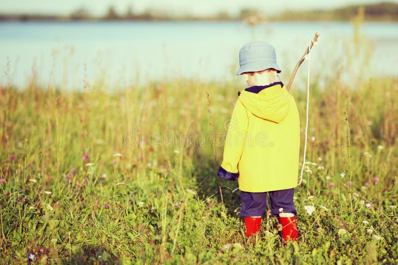 Αγόρι παιδιών με την αλιεία της ράβδου έτοιμης για την αλιεία στοκ εικόνες
