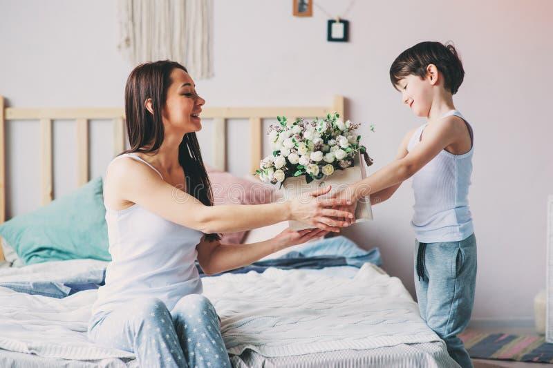 αγόρι παιδιών που δίνει τα λουλούδια στο mom το πρωί για την ημέρα μητέρων στοκ φωτογραφίες