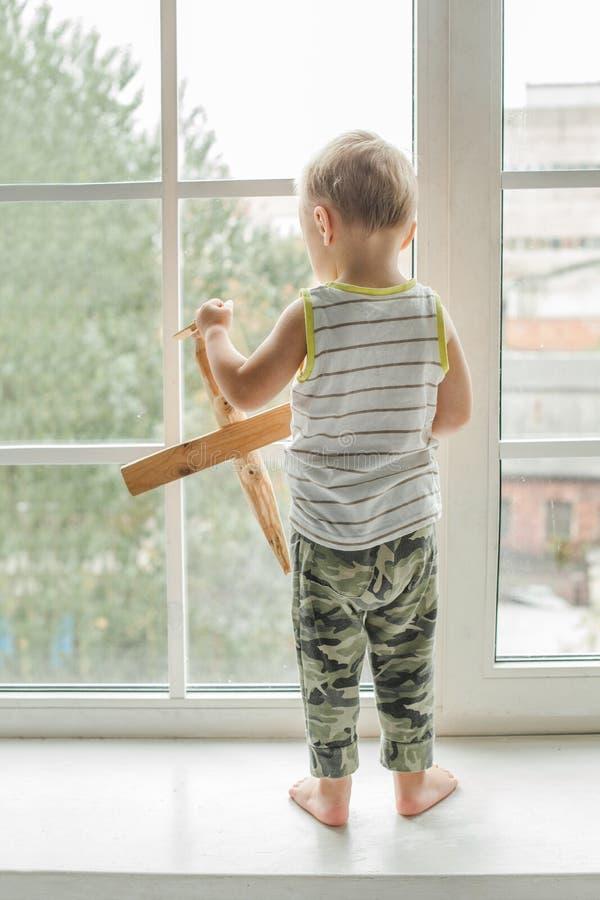 Αγόρι παιδιών που φαίνεται έξω παράθυρο και παιχνίδι στοκ εικόνες