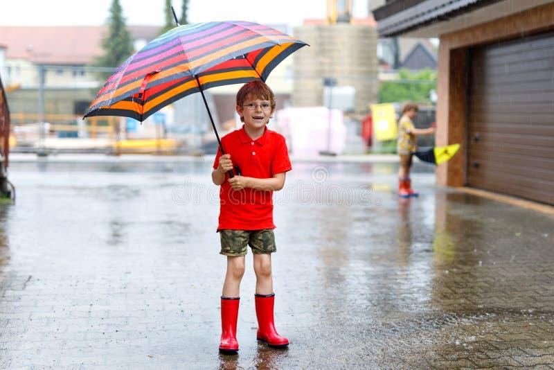 Αγόρι παιδιών που φορά τις κόκκινες μπότες βροχής και που περπατά με τη ζωηρόχρωμη ομπρέλα στην οδό πόλεων Παιδί με τα γυαλιά τη  στοκ εικόνα με δικαίωμα ελεύθερης χρήσης