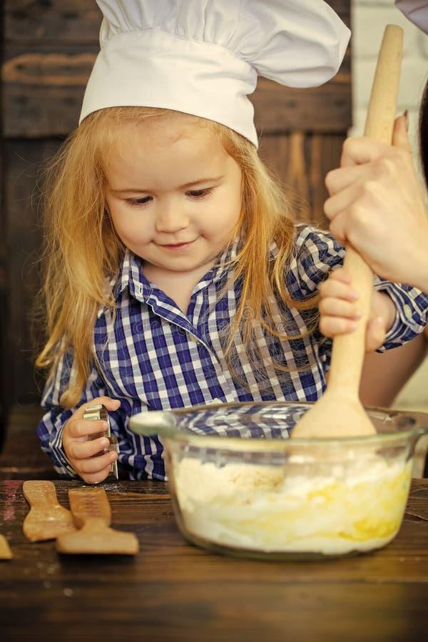 Αγόρι παιδιών στο καπέλο αρχιμαγείρων που αναμιγνύει τη ζύμη με το ξύλινο κουτάλι στοκ φωτογραφία