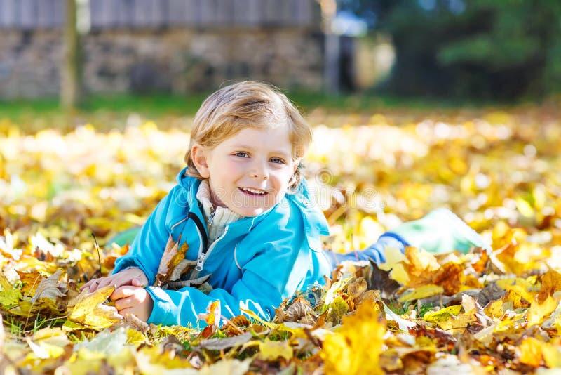 Αγόρι παιδάκι με τα κίτρινα φύλλα φθινοπώρου στο πάρκο στοκ φωτογραφία με δικαίωμα ελεύθερης χρήσης