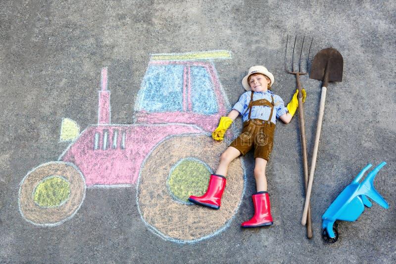 Αγόρι παιδάκι που έχει τη διασκέδαση με την εικόνα κιμωλιών τρακτέρ απεικόνιση αποθεμάτων