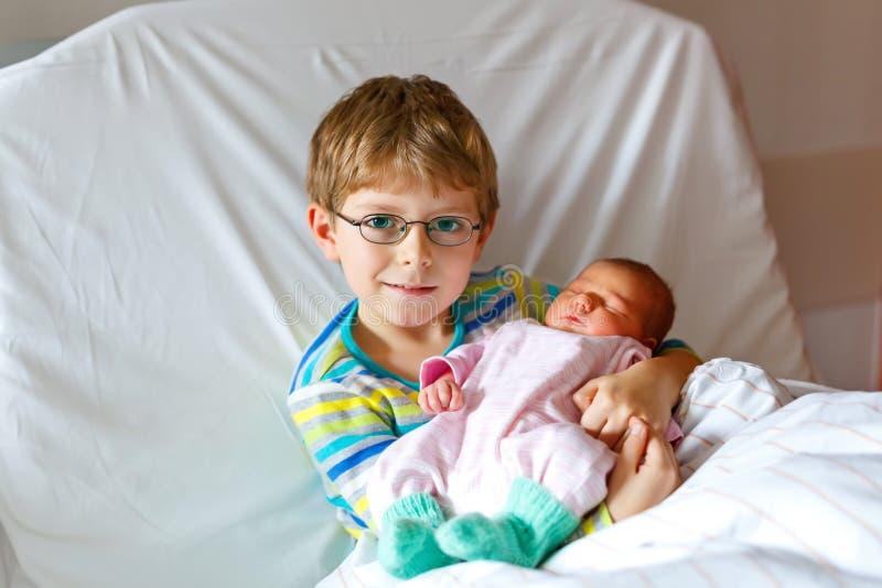 Αγόρι παιδάκι που κρατά τη νεογέννητη αδελφή μωρών ύπνου του στο νοσοκομείο στοκ εικόνες με δικαίωμα ελεύθερης χρήσης