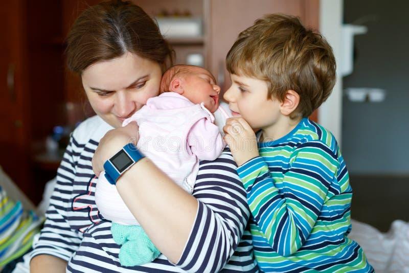 Αγόρι παιδάκι που φιλά τη νεογέννητη αδελφή Μωρό εκμετάλλευσης μητέρων στο βραχίονα στοκ εικόνες