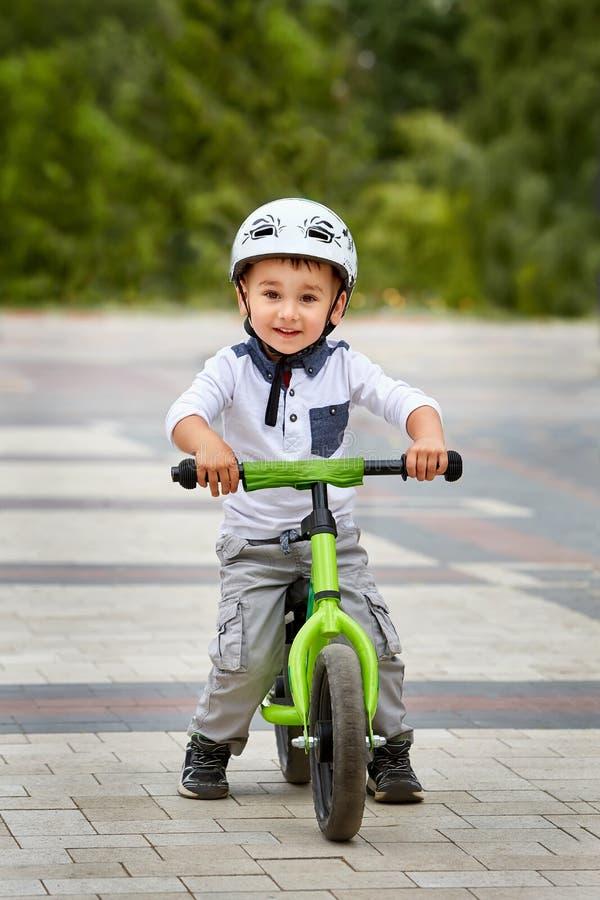 Αγόρι παιδιών στο άσπρο κράνος που οδηγά στο πρώτο ποδήλατό του με ένα κράνος ποδήλατο χωρίς πεντάλια στοκ φωτογραφίες