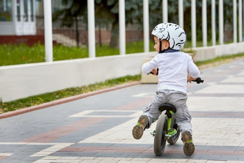 Αγόρι παιδιών στο άσπρο κράνος που οδηγά στο πρώτο ποδήλατό του με ένα κράνος ποδήλατο χωρίς πεντάλια στοκ εικόνα με δικαίωμα ελεύθερης χρήσης