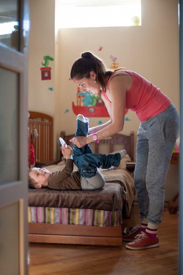 Αγόρι παιδιών φορεμάτων μητέρων στοκ φωτογραφία με δικαίωμα ελεύθερης χρήσης