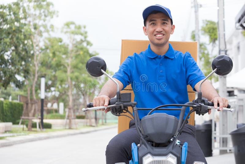 Αγόρι παράδοσης στη μοτοσικλέτα με την οδήγηση κιβωτίων δεμάτων κορμών γρήγορα στη βιασύνη Αγγελιαφόρος που παραδίδει τη διαταγή  στοκ φωτογραφίες
