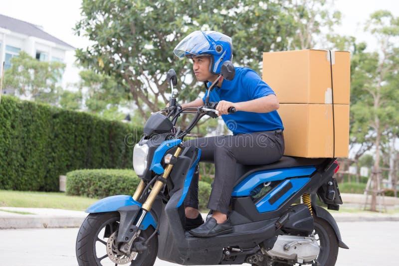 Αγόρι παράδοσης στη μοτοσικλέτα με την οδήγηση κιβωτίων δεμάτων κορμών γρήγορα στη βιασύνη Αγγελιαφόρος που παραδίδει τη διαταγή  στοκ εικόνες με δικαίωμα ελεύθερης χρήσης