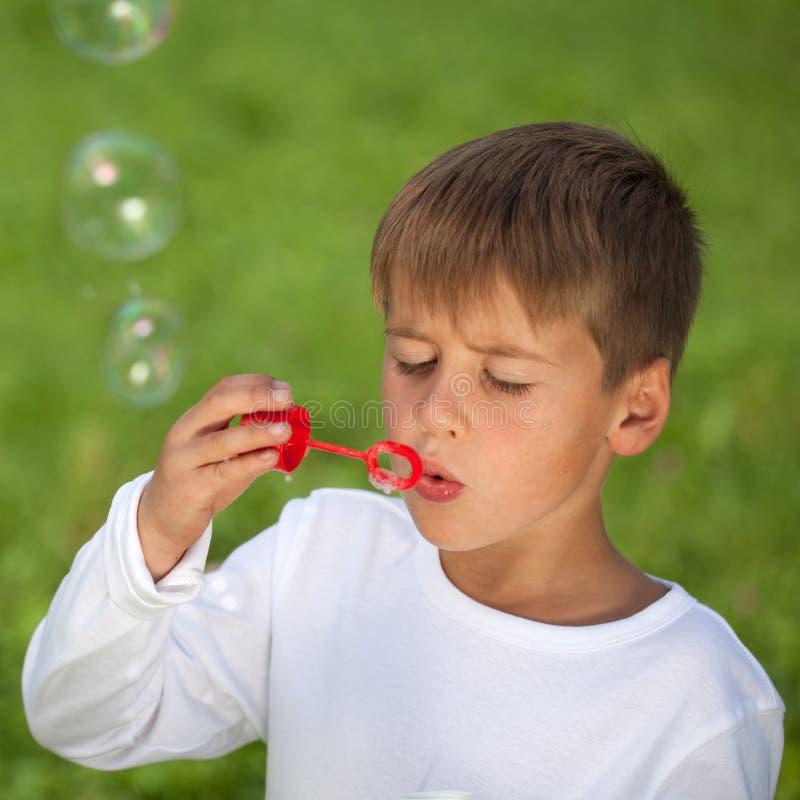 Αγόρι που έχει τη διασκέδαση με τις φυσαλίδες σε ένα πράσινο λιβάδι στοκ φωτογραφία με δικαίωμα ελεύθερης χρήσης