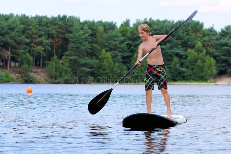Αγόρι που έχει τη διασκέδαση με τη στάση επάνω στο κουπί στη λίμνη στοκ φωτογραφίες με δικαίωμα ελεύθερης χρήσης