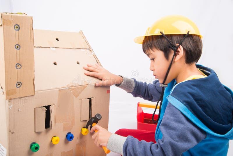 Αγόρι που έχει τη διασκέδαση που χτίζει ένα σπίτι κουκλών εγγράφου στοκ φωτογραφία