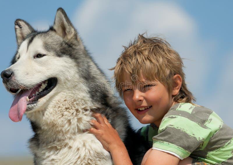 Αγόρι που αγκαλιάζει ένα χνουδωτό σκυλί στοκ εικόνες