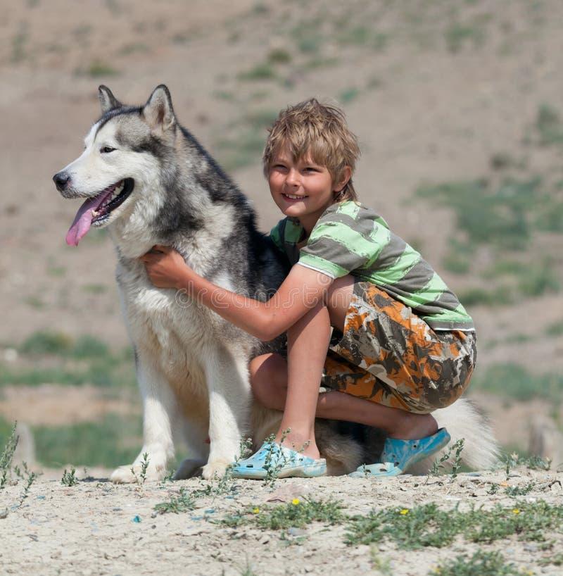 Αγόρι που αγκαλιάζει ένα χνουδωτό σκυλί στοκ εικόνες με δικαίωμα ελεύθερης χρήσης