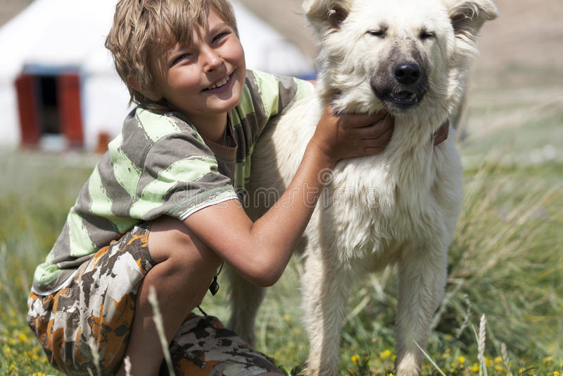 Αγόρι που αγκαλιάζει ένα χνουδωτό σκυλί στοκ εικόνα
