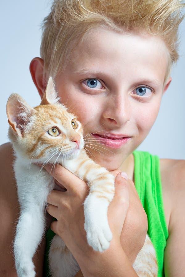 Αγόρι που αγκαλιάζει το γατάκι πιπεροριζών στοκ εικόνες