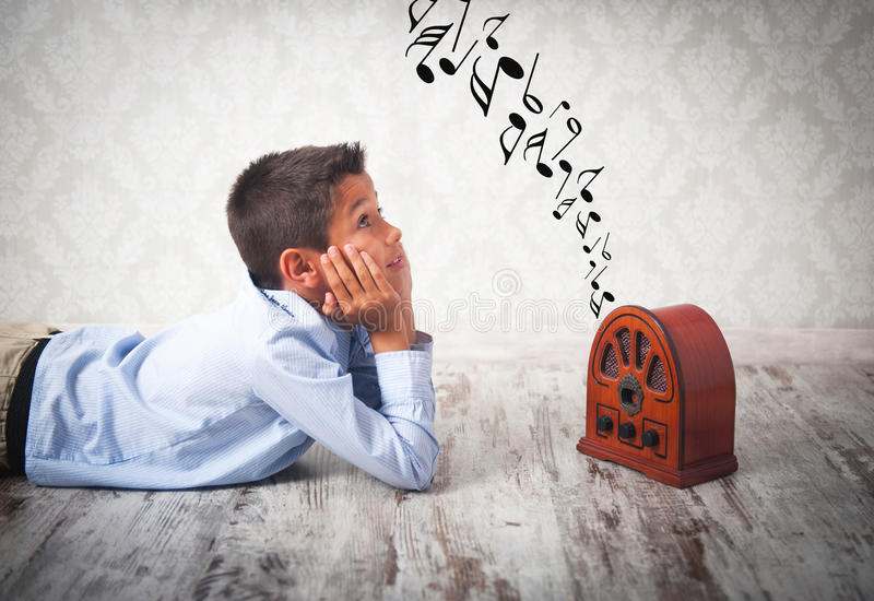 αγόρι που ακούει το αναδρομικό ραδιόφωνο στοκ εικόνες