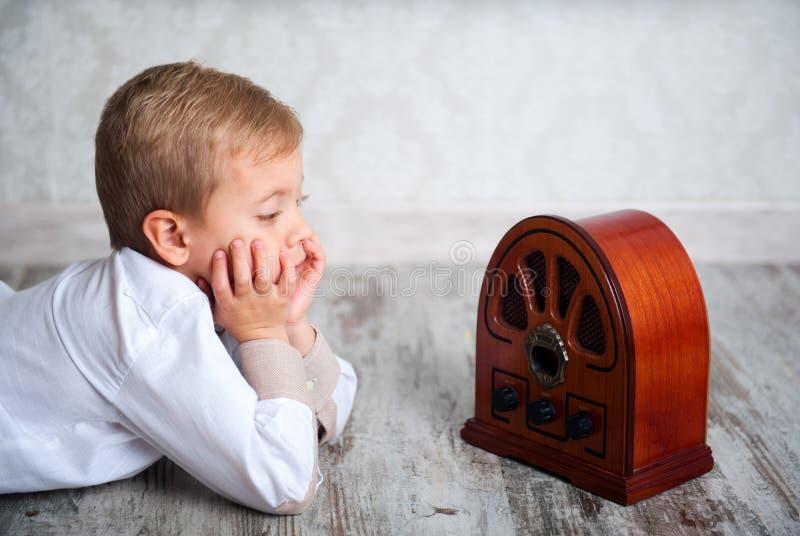 Αγόρι που ακούει το αναδρομικό ραδιόφωνο στοκ φωτογραφίες με δικαίωμα ελεύθερης χρήσης