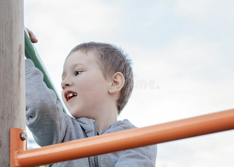 Αγόρι που αναρριχείται στην παιδική χαρά παιδιών υπαίθρια Προσχολικό παιδί που έχει τη διασκέδαση στην παιδική χαρά Παιχνίδι παιδ στοκ εικόνες