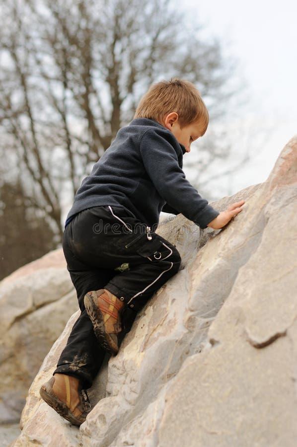 αγόρι που αναρριχείται στις νεολαίες βράχου στοκ εικόνες