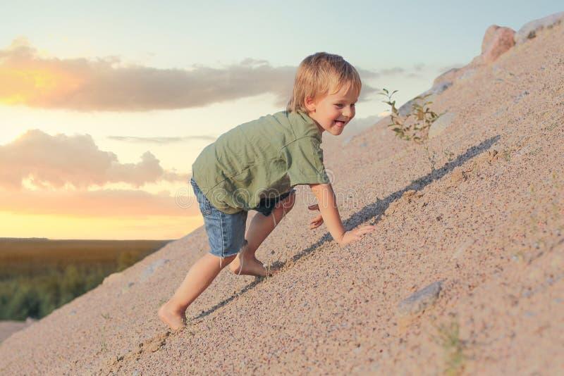 Αγόρι που αναρριχείται στον αμμόλοφο άμμου δέντρο πεδίων στοκ φωτογραφίες