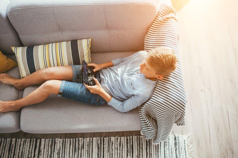 Αγόρι που βάζει στα παιχνίδια καναπέδων με τις ηλεκτρονικές συσκευές - gamepad συνδεμένος με το smartphone στοκ εικόνα